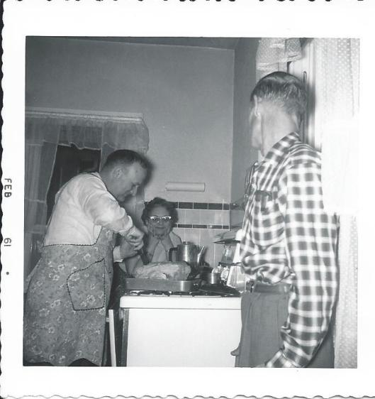 Uncle George carves Christmas turkey while Aunt Wilma and Archie watch 1961